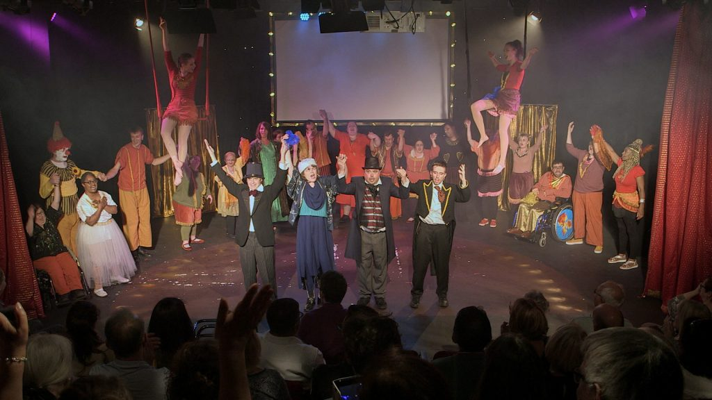 The whole cast of 'The Myth of Marvo's Millions' take a bow at the end of their performance in front of a packed audience who we can see from behind. The audience are clapping wildly while actors from Face Front's 'Broken Silence' inclusive drama group for disabled adults are smiling triumphantly. They stand are wearing costumes of circus performers. This production was part of 'Face Front Fest' in 2019, which took place in Enfield's Dugdale Theatre.